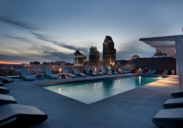 Piscine sur le toit avec plusieurs chaises longues et la vue sur le centre-ville de Montréal