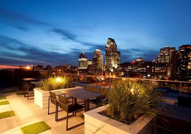 Terrasse sur le toit avec des chaises et tables avec vue sur le centre-ville de Montréal de nuit.