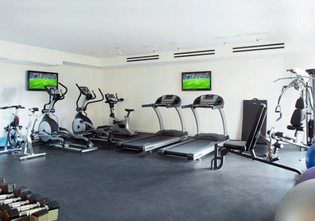 Salle d'entrainement avec machines et tapis.