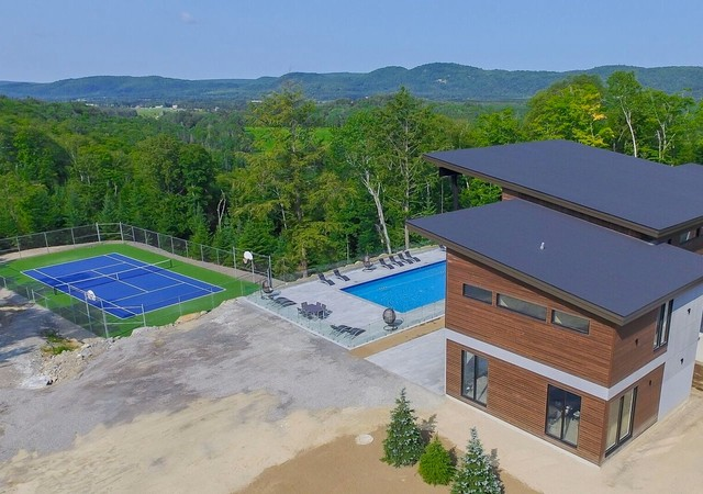 Aerial view of the clubhouse with a pool and a tennis court