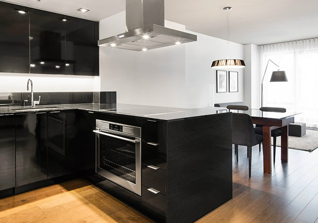 Black kitchen with dining room in background