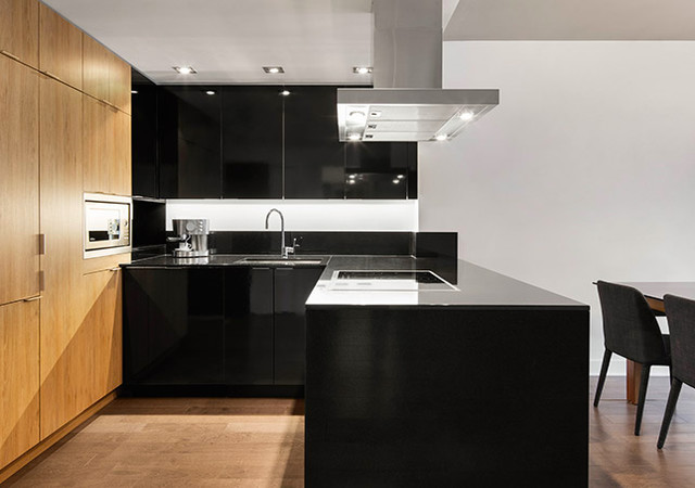 Black kitchen with a wooden wall