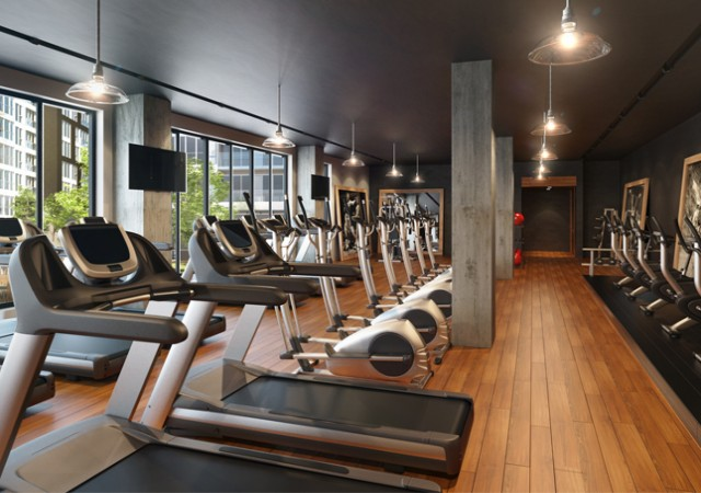 Gym with multiple training machines, a television and large windows