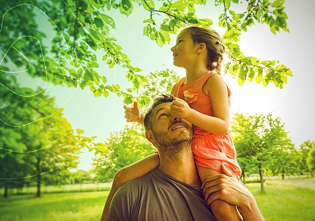 Father playing with daughter in park