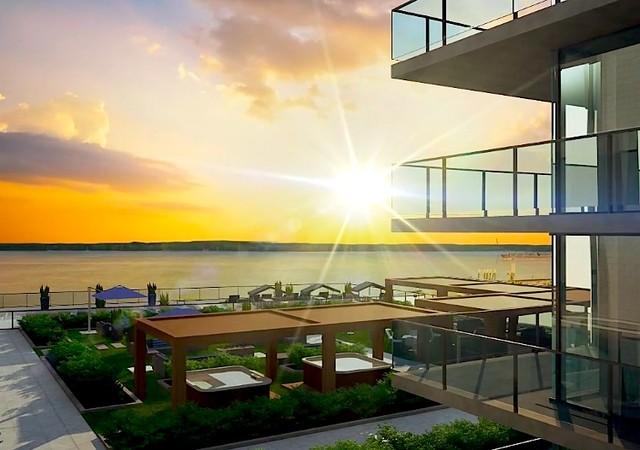 Bâtiment de condo avec le coucher de soleil sur le fleuve