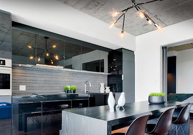 Cuisine avec armoires noires et grand comptoir lunch